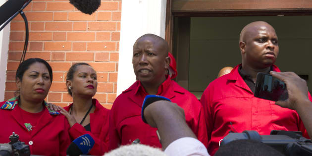 EFF leader Julius Malema (C) and fellow EFF members of Parliament answer journalists' questions as they walk out of the National Assembly on February 16 2018 in Cape Town.