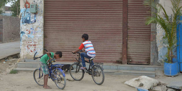 This picture shows children cycling in front of a closed liquor shop near a national highway on the outskirts in Amritsar.