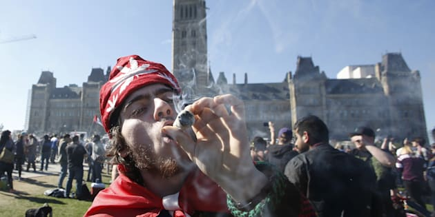 A man smokes marijuana during an annual 4/20 rally on Parliament Hill in Ottawa on April 20, 2016.