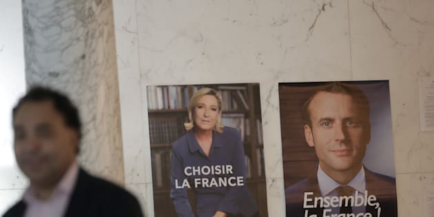 A poll worker stands next to posters for presidential candidates Marine Le Pen and Emmanuel Macron during the second round of the French presidential election at the French Consulate in New York, U.S. May 6, 2017. REUTERS/Joe Penney