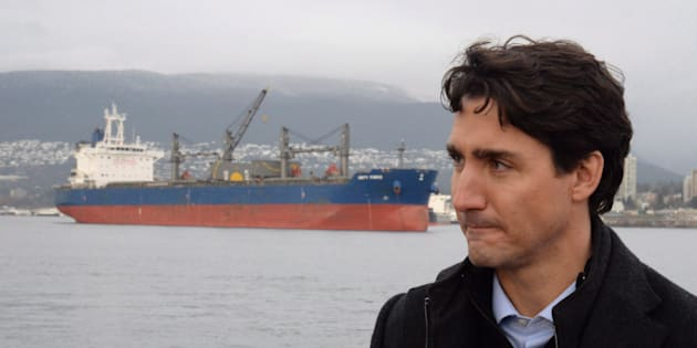 A freighter is seen in the background as Prime Minister Justin Trudeau tours a tugboat in Vancouver Harbour, on Dec. 20, 2016.