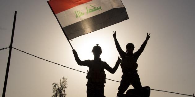 Due agenti della polizia federale irachena innalzano la bandiera nazionale per celebrare la liberazione dell'antica città di Mosul.