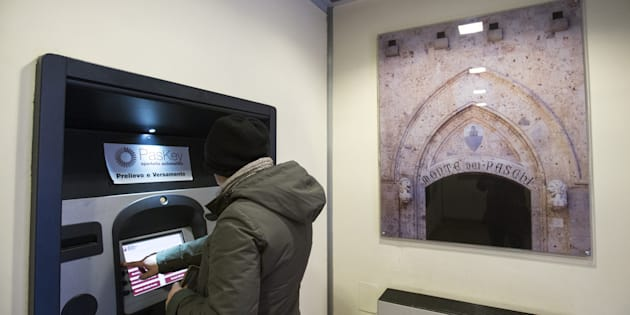 A customer uses a Bancomat automated teller machine (ATM) inside a Banca Monte dei Paschi di Siena SpA bank branch in Siena, Italy, on Friday, Dec. 16, 2016. The bank will begin taking orders for shares Monday as it aims to complete raising 5 billion euros ($5.2 billion) by the end of the year to avoid a rescue by the Italian government. Photographer: Alessia Pierdomenico/Bloomberg via Getty Images