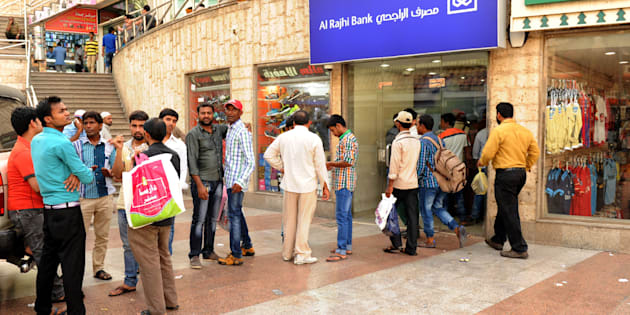 Indian workers queue outside a bank branch in the Saudi Arabian port city of Jeddah on August 4, 2016.