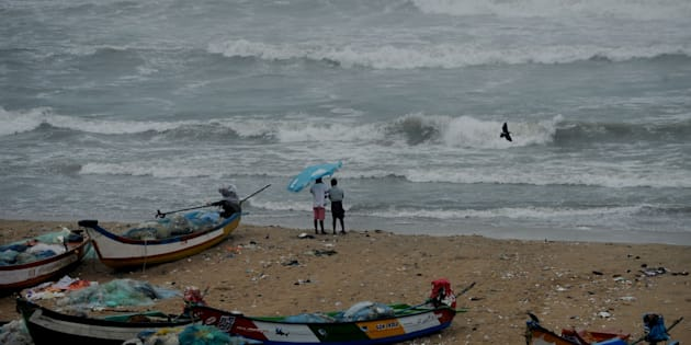 Residents walk near boats as waves break on the cost of the Bay of Bengal in Chennai.