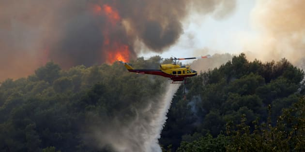 A helicopter drops water as flames and smoke from a burning wildfire fills the sky in Carros, near Nice, France, July 24, 2017.   REUTERS/Eric Gaillard