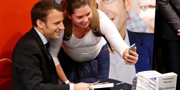 """Emmanuel Macron pose pour un selfie avec une femme venue lui demander un autographe pour son livre """"Révolution"""", le 24 novembre 2016 à Paris."""