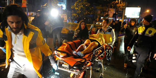 First aid officers carry an injured woman at the site of an armed attack on January 1, 2017 in Istanbul.