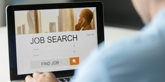 Monitor view over a male shoulder, job search title on the screen, close up. Education, business concept photo