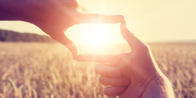 Woman hands framing distant sun rays
