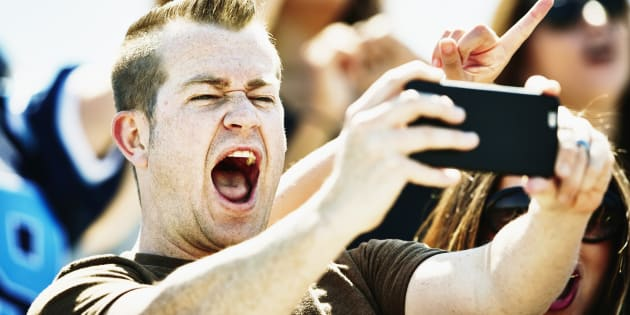 Man celebrating in stadium at football game taking selfie with smartphone