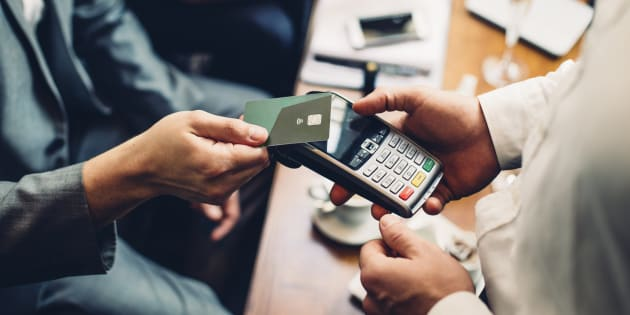 Close up of a card payment being made betweem a man and a waiter in a cafe.