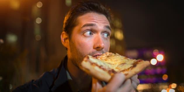 Un homme mange une pizza dans la rue.