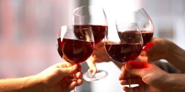 Close-up of four people's hands toasting with wine glasses