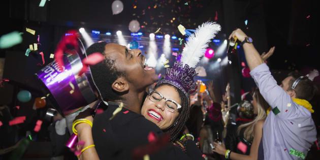 Confetti falling hugging couple enjoying New Year celebration