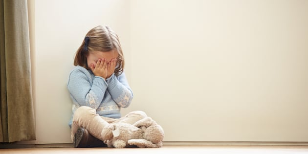 Unhappy Child Sitting On Floor In Corner Crying To Herself At Home