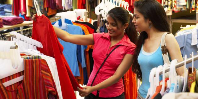 Salesgirl showing dress to woman in supermarket