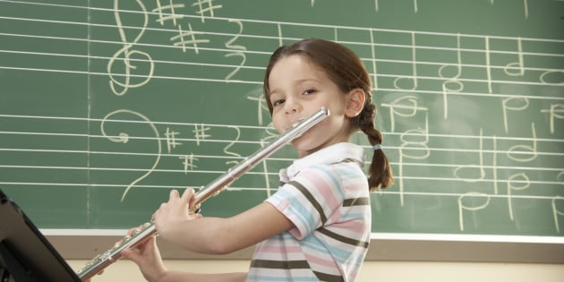 Schoolgirl (5-10) playing flute, smiling, portrait