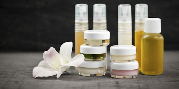 Various jars and bottles of skin care products with orchid flower.