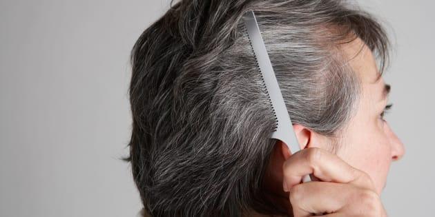 Mature woman combing hair, close-up