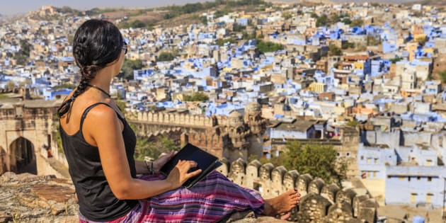 Young female tourist using digital tablet. The blue city of Jodhpur on the background. Jodhpur is known as the Blue City due to the vivid blue-painted houses around the Mehrangarh Fort.