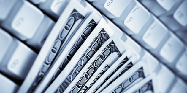 Close-up of US paper currency on a computer keyboard