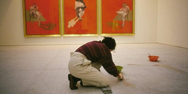 Una mujer limpia el suelo de una galería de arte, ante obras de Francis Bacon.