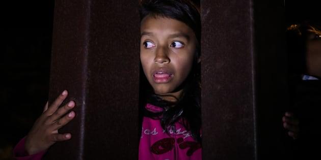 Una migrante tratando de cruzar la valla que divide México de EE UU.