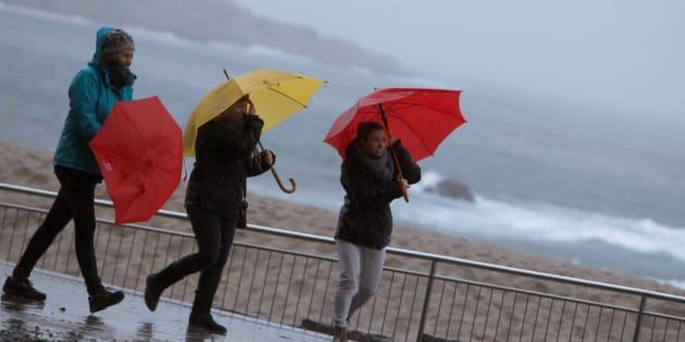 Tres mujeres se protegen de la lluvia en el paseo marítimo de A Coruña, el pasado domingo.