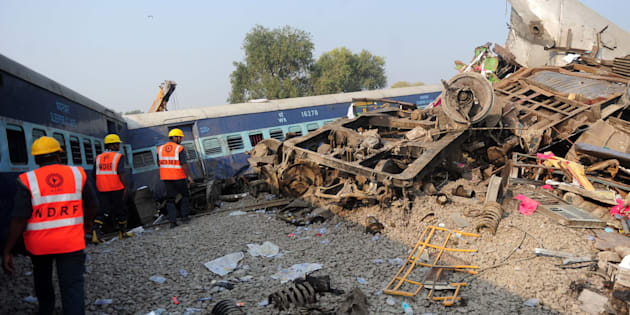 Indian rescue workers search for survivors in the wreckage of a train that derailed near Pukhrayan.