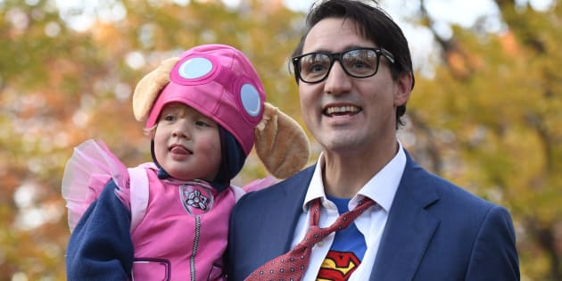 "Prime Minister Justin Trudeau, dressed as Clark Kent, holds his son Hadrien, dressed as Skye from ""Paw Patrol,"" as they go trick-or-treating on Halloween in Ottawa on Tuesday."