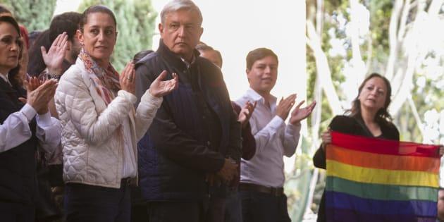 Una mujer muestra una bandera del orgullo gay a Andrés Manuel López Obrador durante un mitin en CDMX.