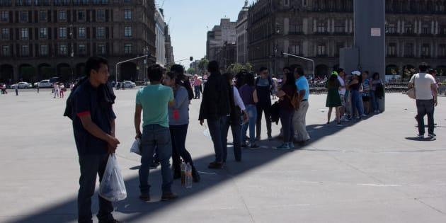 Capitalinos se resguardan del sol en la sombra del asta en la plancha del Zócalo.
