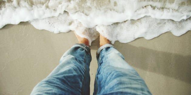 Standing on beach, sea surf.