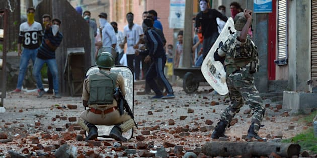 An Indian security offciers throws a stone to Kashmiri protestors during a clash in Batmaloo area of Srinagar on July 28, 2016.