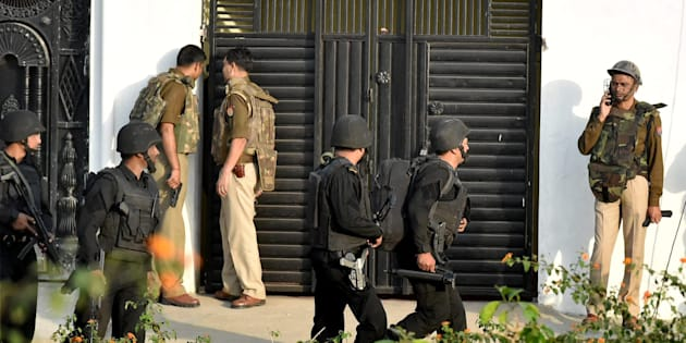 Uttar Pradesh Anti Terror Squad members take positions near a building where a suspected terrorist was holed up in the Thakurganj area of Lucknow on Tuesday evening.