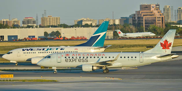 Air Canada and WestJet planes taxiing at Toronto Pearson International Airport, Wed. July 20, 2016. Many Canadians will be forced to spend a little more to travel after Air Canada and WestJet Airlines Ltd. said they are increasing fees for passengers to check their bags.