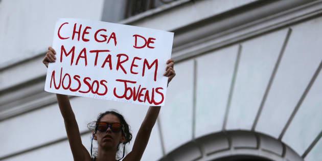 """Mulher levanta o cartaz com dizeres """"Chega de matarem nossos jovens"""", em protesto no Rio de Janeiro após o assassinato da vereadora Marielle Franco."""