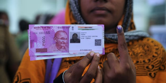 Woman poses with new ₹2,000 notes, her Aadhaar ID card and a finger inked with indelible ink after exchanging withdrawn ₹500 and ₹1,000 banknotes.