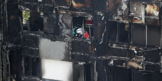 A firefighter examines material in a tower block severely damaged by a serious fire, in north Kensington, West London, Britain June 14, 2017. REUTERS/Neil Hall
