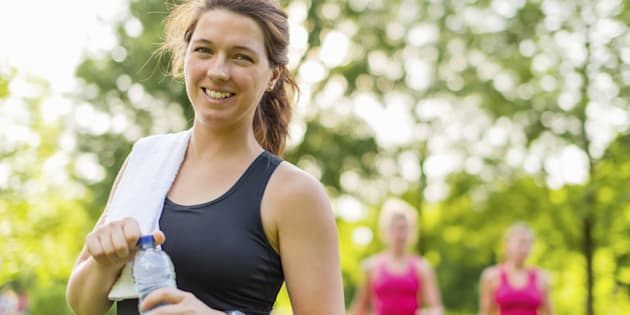 Athlete drinking water from a bottle after a workout in nature