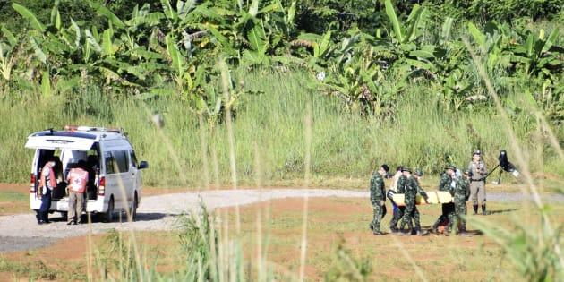 Des secouristes portant un garçon sauvé de la grotte de Tham Luang dans la province de Chiang Rai, au nord de la Thaïlande, le 9 juillet 2018.