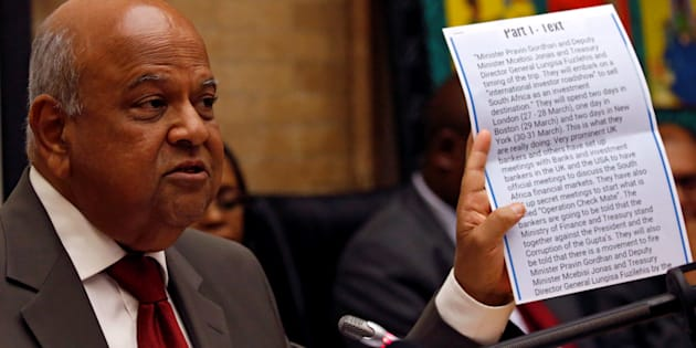 Former finance minister Pravin Gordhan holds a copy of a fake intelligence report that President Jacob Zuma used as justification to fire him, during a media briefing at their offices in Pretoria, South Africa, March 31,2017.
