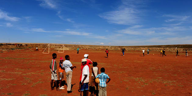 Children watch others enjoying a game of football on June 15, 2009 in Mogale City, South Africa.