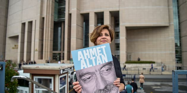 A journalist poses with a portrait of Turkish journalist Ahmet Altan on June 19, 2017 in front of the Istanbul courthouse, where his trial is to take place.