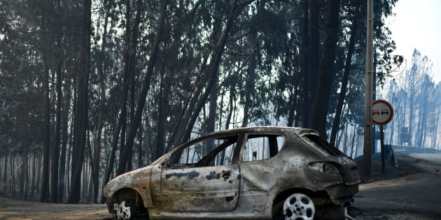 A picture taken on June 18, 2017 shows a burnt car on a road after a wildfire in Pedrogao, in central Portugal. A wildfire in central Portugal killed at least 57 people and injured 59 others, most of them burning to death in their cars, the government said on June 18, 2017. Several hundred firefighters and 160 vehicles were dispatched late on June 17 to tackle the blaze, which broke out in the afternoon in the municipality of Pedrogao Grande before spreading fast across several fronts.    / AFP PHOTO / PATRICIA DE MELO MOREIRA        (Photo credit should read PATRICIA DE MELO MOREIRA/AFP/Getty Images)