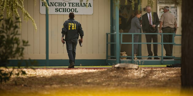 FBI agents are seen behind yellow crime scene tape outside Rancho Tehama Elementary School after a shooting in the morning on November 14, 2017, in Rancho Tehama, California