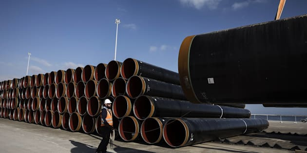 A worker holds a rope as he guides the loading of a pipe section for the Trans Adriatic gas pipeline onto a transport truck on the dockside at the cargo port of Alexandroupolis, Greece, on Feb. 23, 2017. The Trans Adriatic Pipeline AG (TAP) will transport Caspian natural gas to Europe crossing Northern Greece, Albania and the Adriatic Sea coming ashore in Southern Italy to connect the Italian gas network to the Trans Anatolian Pipeline (TANAP). Photographer: Konstantinos Tsakalidis/Bloomberg via Getty Images