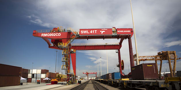 A loading crane straddles a freight rail track near shipping containers on the opening day of Transnet SOC Ltd.'s new container handling terminal at City Deep inland port in Johannesburg, South Africa, on Thursday, Nov. 26, 2015. Transnet plans to spend as much as 380 billion rand over the next decade to expand and upgrade rail and port capacity in South Africa, the world's biggest manganese producer and the continents largest source of iron ore and coal. Photographer: Karel Prinsloo/Bloomberg via Getty Images