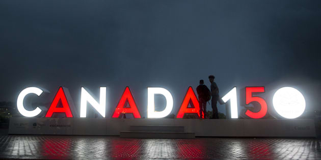 Tourists stand near an illuminated 'Canada 150' sign in Niagara Falls, Ontario, Canada, on Wednesday, June 21, 2017.